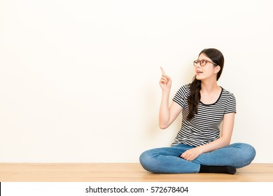 Portrait young woman thinking dreaming has many ideas looking up. Decision making process concept sitting on wooden floor over blank copy space white wall background.