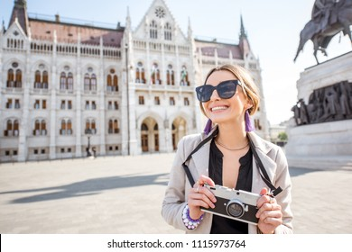 Portrait of a young woman tourist with photo camera in front of the famous Parliament building traveling in Budapest city, Hungary