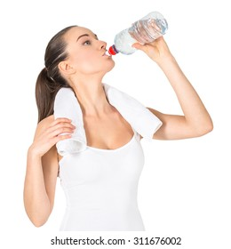 Portrait of a young woman with towel around neck drinking water over white background. Isolated on white.