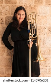 Portrait of a young woman trombonist in ancient urban environment.