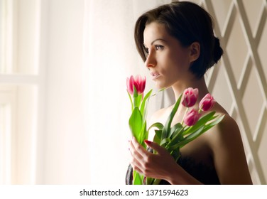 Portrait of  young woman with tulips is standing in light room