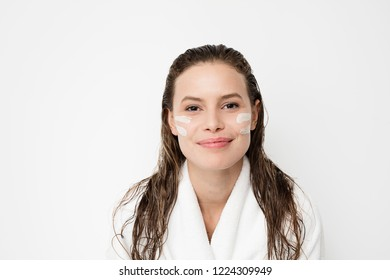 portrait of young woman with two lines of cream skin treatment on her face, smiling to camera with joy and pleasure. with wet hair after a shower in her bathrobe