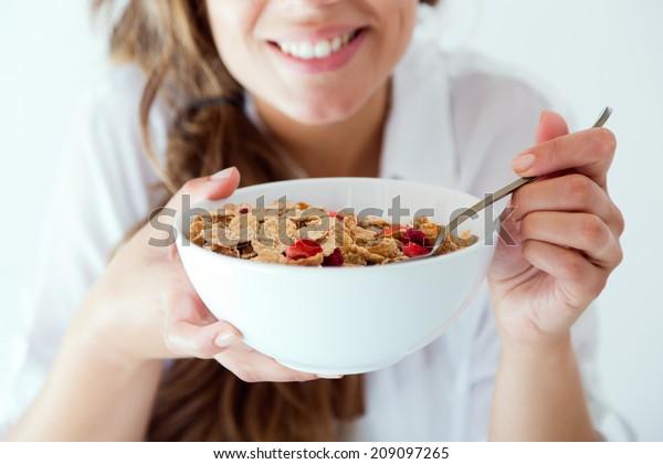 Portrait d'une jeune femme en sous-vêtements mangeant des céréales. Isolé sur blanc.