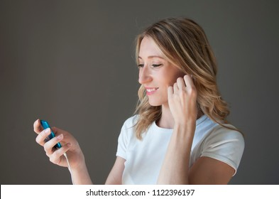 Portrait of young woman using iPod with headphones
