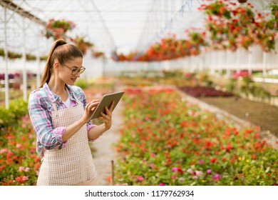 Portrait of young woman using tablet in green garden