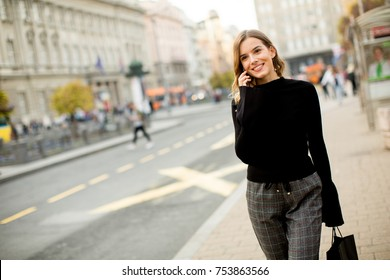 Portrait of young woman waiting for taxi or bus on the street in the city