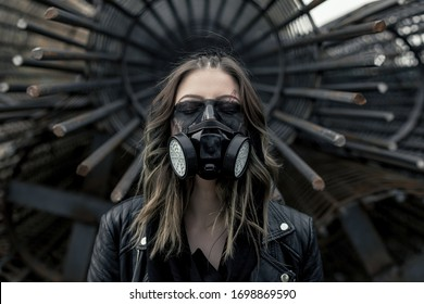 Portrait of a young woman wearing a black respirator, posing outdoors