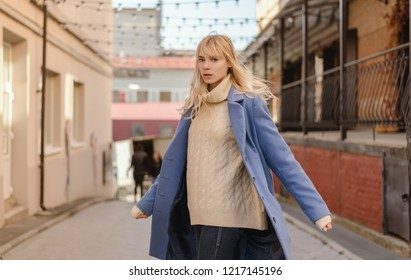 Portrait of young woman wearing blue coat.