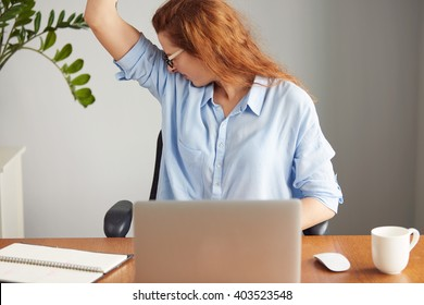 Portrait of a young woman wearing blue shirt disgusting with bad smell of her wet armpit while working in the office. Something stinks, negative human emotions, facial expressions, feeling reaction
