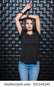 Portrait of young woman wearing blue jeans and black t-shirt