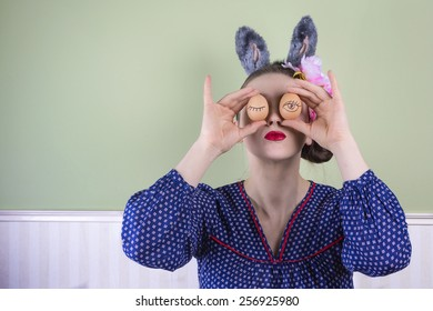 Portrait of a young woman wearing bunny ears holding two eggs in front of her eyes.
