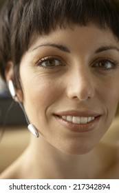 Portrait of a young woman wearing a hands free device and smiling