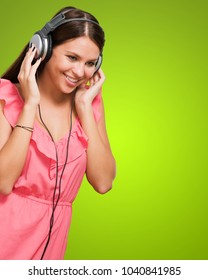 Portrait Of A Young Woman Wearing Headphones against a green background