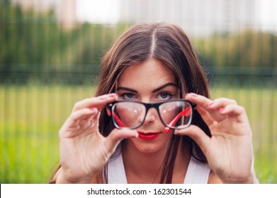 Portrait Of Young Woman Wearing Hipster Glasses On Sport Playground