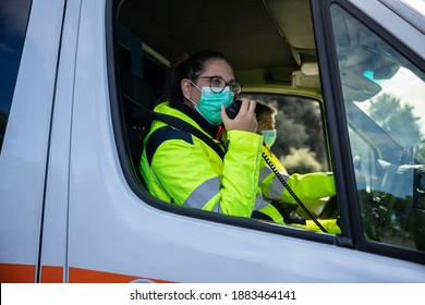 Portrait of a young woman wearing a mask and uniform in an ambulance during a volunteer shift answering an emergency call with her fellow driver - Concept of pandemic from Covid-19, Coronavirus