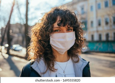 Portrait of a young woman wearing medical facial mask walking in European city on sunny spring day.