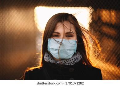 Retrato de una mujer joven que lleva cara protectora con máscara médica mientras está de pie contra la valla al atardecer