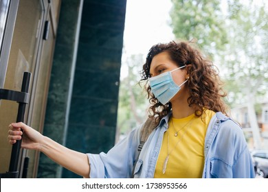Portrait young woman wearing protective medical mask holds on to the handle and opens the door when entering store.