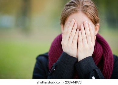 Portrait of a young woman wearing a red scarf and covering her face with her hands. Copy space available.