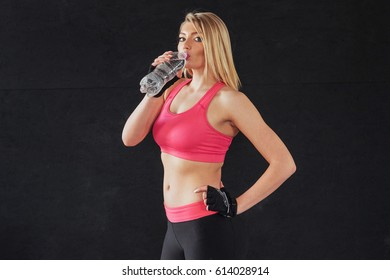 Portrait of a young woman wearing sport clothes and drinking water on a black background