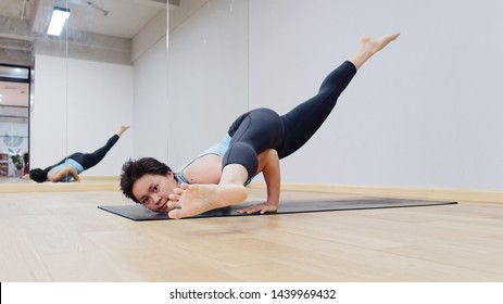 Portrait of young woman wearing sportswear doing strength training on exercise mat. doing balance handstand pose exercises at gym. Difficult posture astavakrasana, asymmetrical arm balance concept