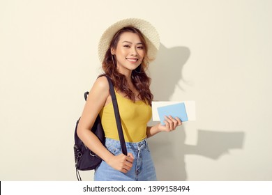 Portrait of young woman wearing trendy outfit, straw hat, travel with backpack  and holding flight ticket, passport