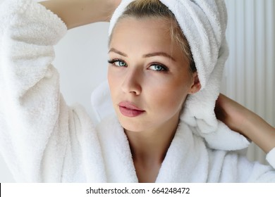 Portrait of young woman wearing white bathrobe standing in the bathroom.Portrait of beautiful girl in bathrobe and with towel on her head