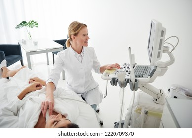 Portrait of young woman in white bathrobe lying on daybed during medical examination while physician looking at monitor and smiling