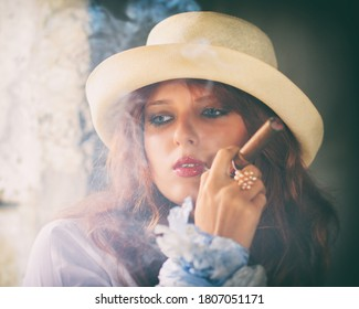 portrait of a young woman in a white hat with a cigar in her hand. Selective focus on the model's eyes. Smoke from a cigar