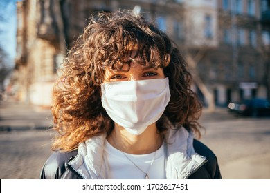 Portrait young woman in white medical protective face mask looking at camera while standing on street in European city.