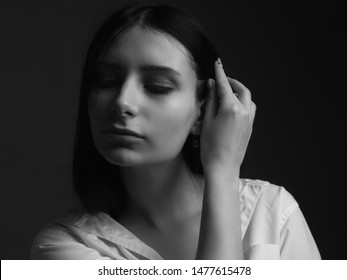 Portrait of young woman in white shirt. Black and white. Low key