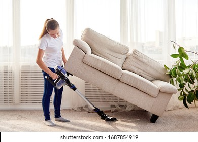 Portrait of young woman in white shirt and jeans cleaning carpet with vacuum cleaner under sofa in living room, copy space. Housework, cleanig and chores concept