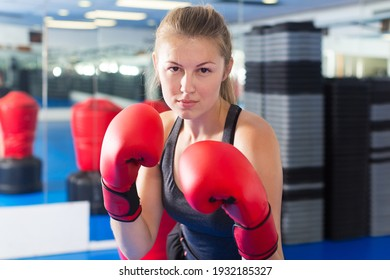 Portrait of young woman who is boxing in gym