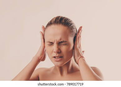 portrait of a young woman who closes her ears with her hands because of strong noise