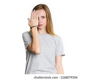 Portrait of a young woman who covered her hand with one eye isolated on a white background.