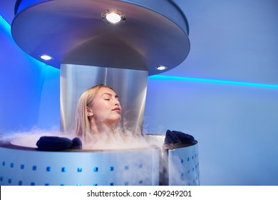 Portrait of young woman in a whole body cryo sauna. Female getting cryo therapy at the cosmetology clinic.