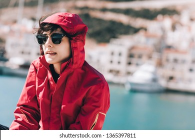 Portrait of young woman in windbreaker jacket with sunglasses