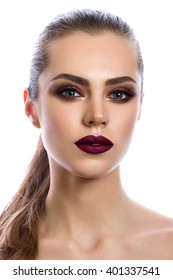 Portrait of young woman with wine red lips and bronze smokey eyes. Modern fashion make-up. Studio shot. Ponytail hairdo