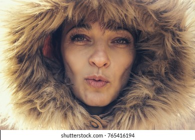 portrait of young woman with winter heat sending kiss
