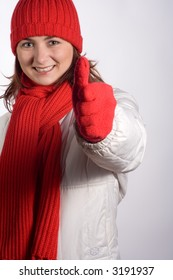 Portrait of a young woman in winter outerwear, doing a thumbs up.