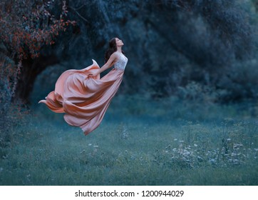 portrait young woman witch floating air spirit power spirituality ghost butterfly. luxury dress waving silk skirt fabric fly wind. Cold blue green grass forest. Enchanted princess Art photo levitation