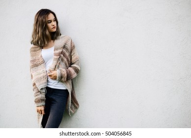 Portrait of a young woman in woolen sweater posing against a white wall