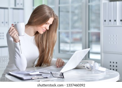 Portrait of young woman working at office, using laptop