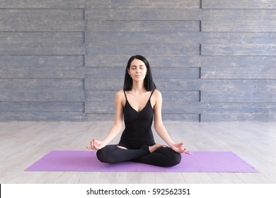 Portrait of young woman working out on fitness mat, doing lotus yoga pose at the gym. Yoga exercise, relax and meditating.