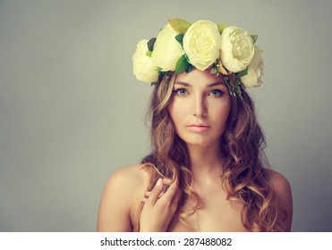 Portrait of a Young Woman with Wreath of Flowers on Gray Background. Natural Beauty Concept. Toned Photo with Copy Space.