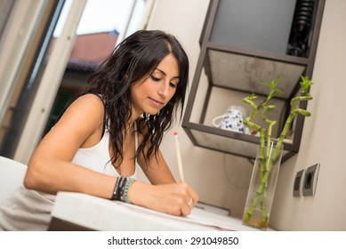 Portrait of young woman writing a letter in hotel room.