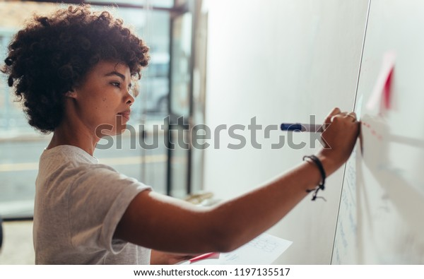 Portrait of young woman writing on white board during a presentation in conference room. Female noting few points on white board during a meeting at startup office.