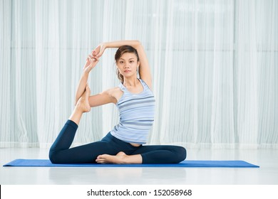 Portrait of a young woman in yoga pose posing at camera