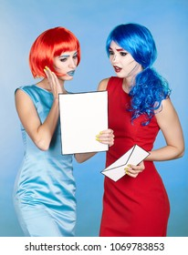 Portrait of young women in comic pop art make-up style. Females in red and blue wigs and dresses are reading letter