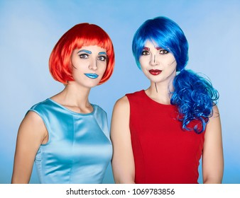 Portrait of young women in comic pop art make-up style. Females in red and blue wigs and dresses